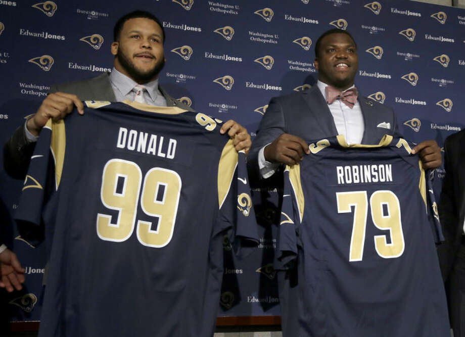 St. Louis Rams first-round draft picks Greg Robinson, right, and Aaron Donald pose for photographers during a news conference at the NFL football team's practice facility Tuesday, May 13, 2014, in St. Louis. Robinson, an offensive tackle from Auburn, was picked second overall and Donald, a defensive tackle from Pittsburgh, was taken 13th overall. (AP Photo/Jeff Roberson)