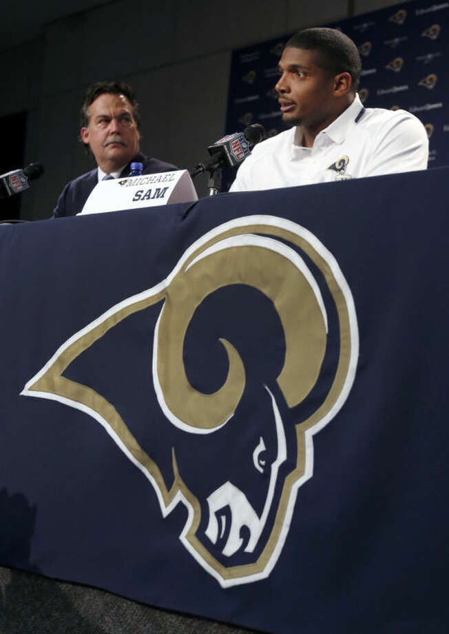 St. Louis Rams seventh-round draft pick Michael Sam, right, speaks as coach Jeff Fisher listens during a news conference at the NFL football team's practice facility Tuesday, May 13, 2014, in St. Louis. (AP Photo/Jeff Roberson)