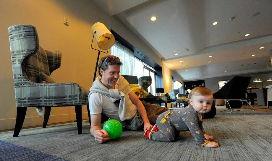 Billy Sparkle plays with his 11-month-old son Primo in a common area for residents of 75 Tresser in Stamford on May 11, 2016.