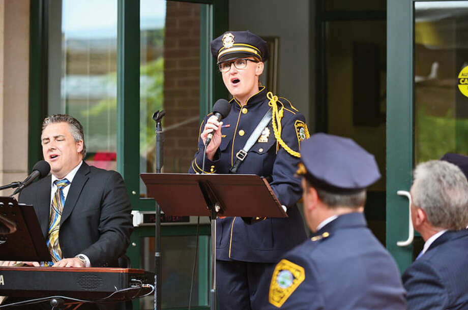 Hour photo / Erik Trautmann Detective Kristina Lapak and David Harris sings as the Norwalk Police Department honors the four Norwalk officers who have given their lives in the line of duty as well as those retired officers the department has lost in the past year in a memorial ceremony Wednesday morning.
