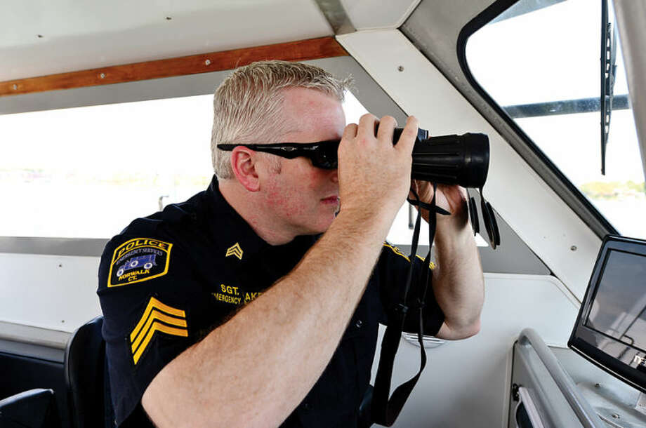 Hour photo / Erik Trautmann Seargant Terry Blake assits the Norwalk Police Department Marine Unit.