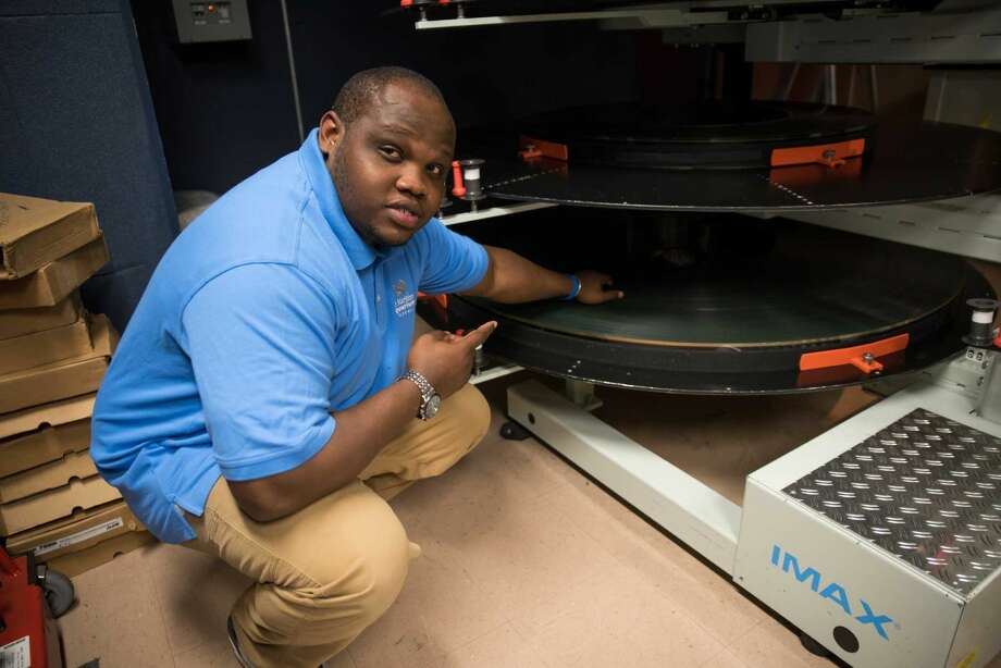 Dwayne Blyden prepares to thread a 70mm film reel into the projector.