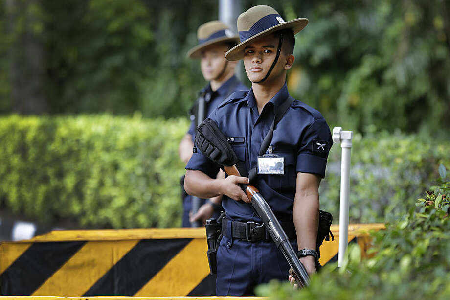 Singapore Gurkha policemen guard the grounds surrounding the venue of the 14th International Institute for Strategic Studies Shangri-la Dialogue, or IISS, Asia Security Summit, Sunday, May 31, 2015, in Singapore. Police stepped up security around the venue of the international security conference Sunday following a shootout at a roadblock in which officers fatally shot one man and detained two others. The security conference, a major event in the Asia-Pacific region attended by U.S. Secretary of Defense Ash Carter and delegates from dozens of countries from around the world, was uninterrupted but access to the venue was restricted. (AP Photo/Wong Maye-E)