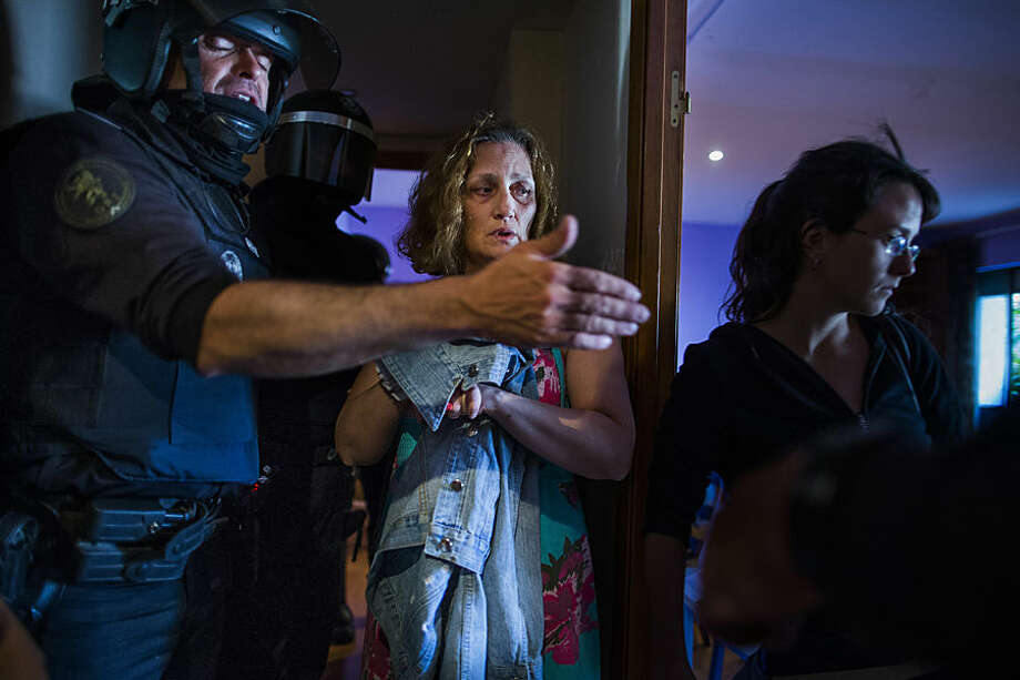 Carmen Rives, 50, center, gestures as riot police enter her apartment to evict her in Madrid, Spain, Tuesday, June 2, 2015. The unemployed woman lost her foreclosed apartment to a moneylender because she could not afford the pay her debt due to her financial situation. The eviction was carried out by dozens of riot police who arrested at least 12 anti-eviction activists. (AP Photo/Andres Kudacki)