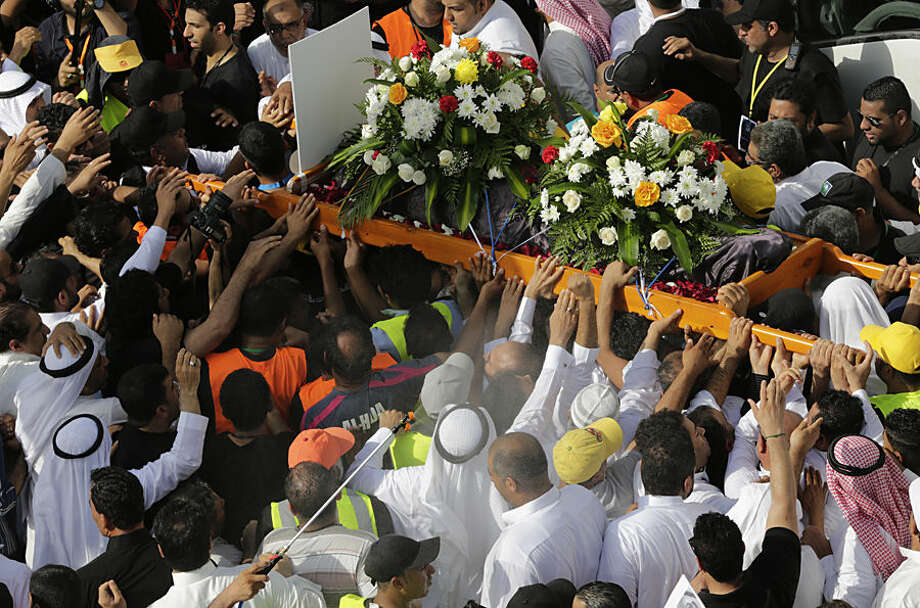 Saudis escort the body of Mansour Fateel, who died of his injuries to become the 22nd victim of a mosque bombing claimed by the Islamic State group, during his funeral Saturday, May 30, 2015, in Tarut, Saudi Arabia. Thousands of Shiites took to the streets of eastern Saudi Arabia to remember the latest victim of the country's deadliest terrorist bombing in years and denounce attacks on their community. (AP Photo/Hasan Jamali)