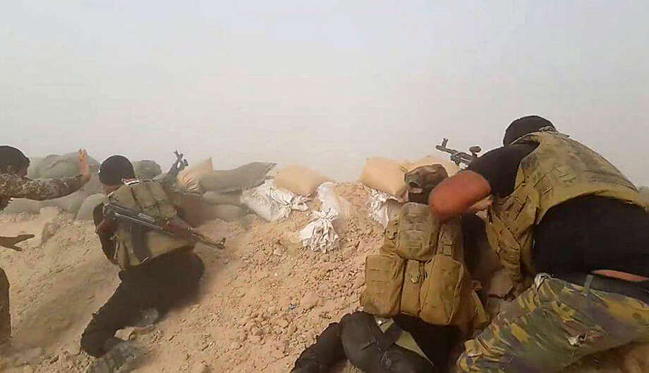 In this image taken Friday, May 29, 2015, Iraqi anti-terrorism forces battle with Islamic State group extremists as they defend their base against Islamic State group extremist attack outside Fallujah, 40 miles (65 kilometers) west of Baghdad, Iraq. (AP Photo)