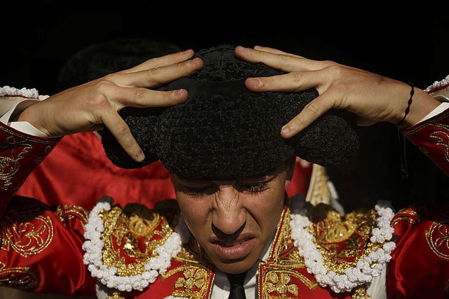 In this photo taken Saturday, May 30, 2015, Spanish bullfighter Alvaro Lorenzo adjusts his montera hat before a bullfight with Alcurrucen ranch fighting bulls in Aranjuez, near Madrid, Spain. Bullfighting is an ancient tradition in Spain. (AP Photo/Daniel Ochoa de Olza)