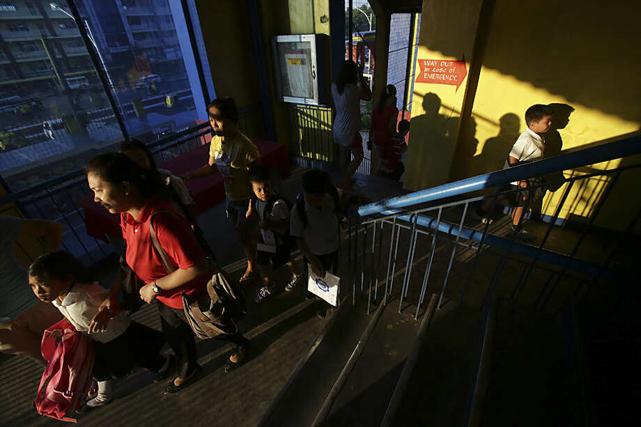 Filipino grade school students look for their rooms during the first day of school at the President Corazon C. Aquino Elementary School in suburban Quezon City, north of Manila, Philippines Monday, June 1, 2015. More than 23 million students trooped back to school Monday amid perennial problems like overcrowded classrooms and lack of teachers and desks. (AP Photo/Aaron Favila)