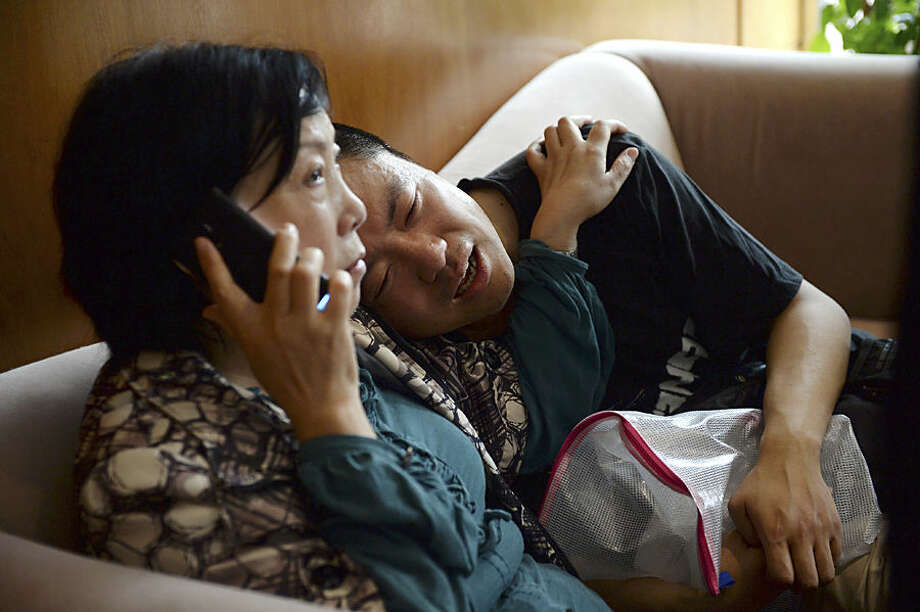 A man grieves for his missing parents as his aunt calls on her phone outside a travel agency which was involved in organizing a Yangtze River cruise, in Shanghai, China Tuesday June 2, 2015. A small cruise ship sank overnight in China's Yangtze River during a storm, state media said Tuesday. (Chinatopix via AP) CHINA OUT