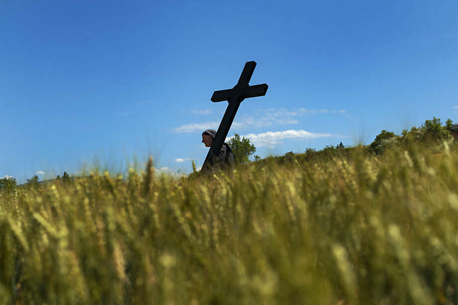Bernardo Aoiz, a penitent 57, walks through a field holding his cross during a march of the Trinidad brotherhood in Lumbier, northern Spain, Sunday, May 31, 2015. Every year devotees march from their small town to a Trinity Chapel where they receive a blessing. (AP Photo/Alvaro Barrientos)