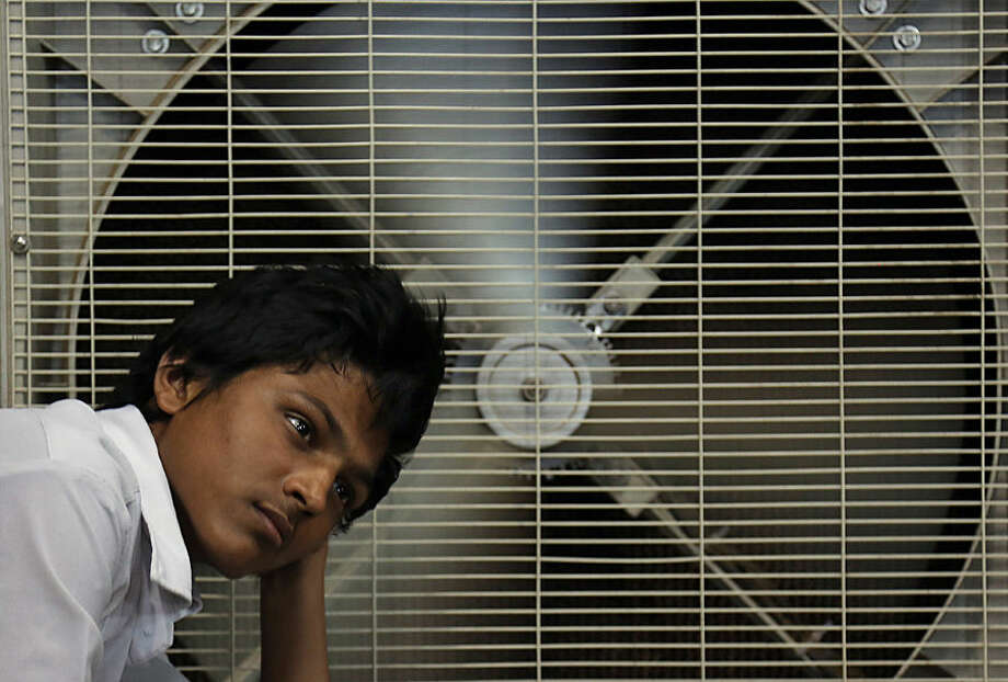 An Indian man rests in front of an air cooler to cool himself on a hot summer day in Hyderabad, in the southern Indian state of Telangana, Sunday, May 31, 2015. Isolated thundershowers have failed to break a raging heat wave in the southern Indian states of Andhra Pradesh and Telangana, claiming dozens of lives over the weekend and raising the overall death toll to more than 2,000 since mid-April. (AP Photo/Mahesh Kumar A.)