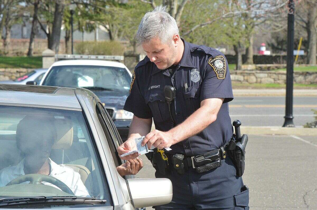 Hour Photo/Alex von Kleydorff Norwalk Police Officers Norwalk Police Officer Jamie Wright issues a ticket to a driver after she was observed by an officer stationed one block north, on West Ave. on her cell phone during distracted driving enforcement on Tuesday