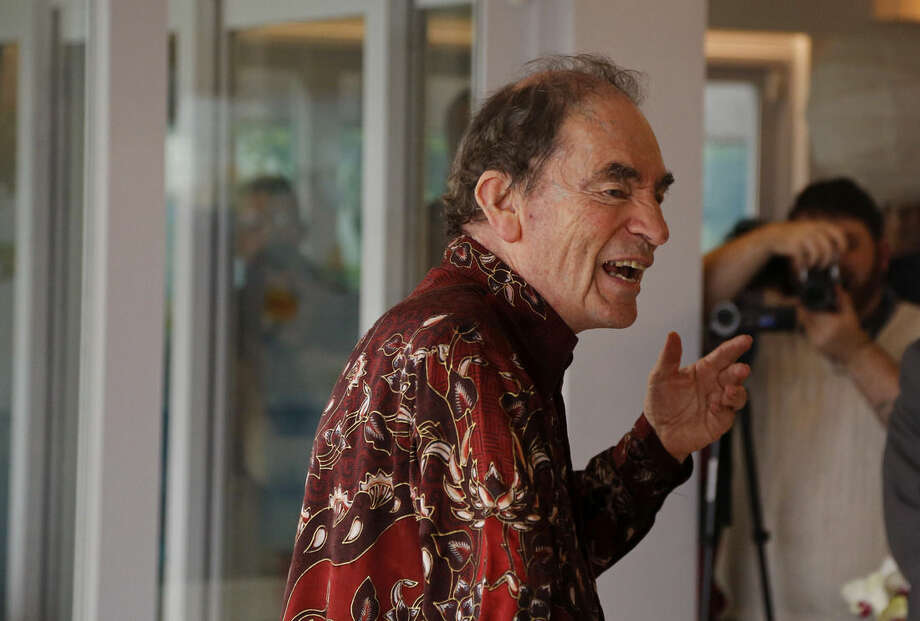 South African Albie Sachs, a former judge and anti-apartheid activist speak at his Clifton home to researchers, diplomats and journalists who attended a tribute Tuesday June 2, 2015 to slaves that died in 1794 as their ship sank near his home on the outskirts of the city of Cape Town, South Africa, Against a backdrop of exclusive, sea-view apartments in Cape Town, South African and American researchers paid tribute to slaves who died when the Portuguese ship that was carrying them into bondage sank just off the coastline while sailing to Brazil in 1794. (AP Photo/Schalk van Zuydam)