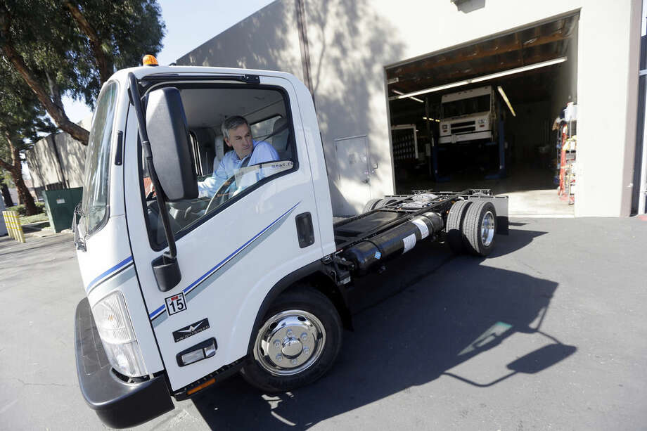 Wrightspeed CEO Ian Wright drives an electric-powered truck at the company's headquarters Thursday, Feb. 12, 2015, in San Jose , Calif. Wright helped bring electric cars to market when he co-founded Tesla Motors a decade ago. Now he's targeting trucks that deliver packages, haul trash and make frequent stops on city streets. His company, Wrightspeed, makes electric powertrains that can be installed on commercial trucks, making them more energy-efficient. (AP Photo/Marcio Jose Sanchez)