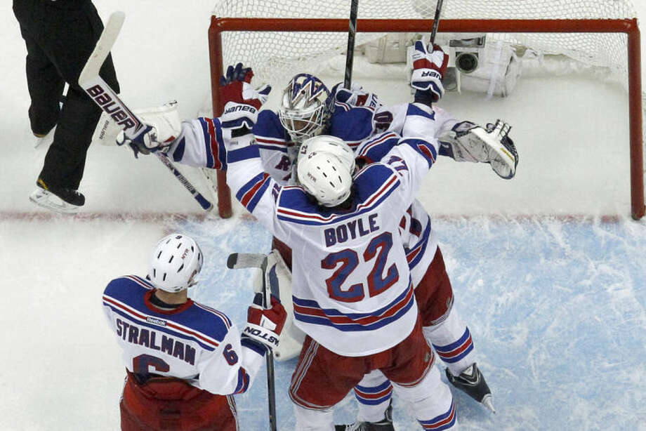 New York Rangers goalie Henrik Lundqvist (30) begins to celebrate with teammates Brian Boyle (22) and Anton Stralman (6) as time runs out in Game 7 of a second-round NHL playoff hockey series against the Pittsburgh Penguins in Pittsburgh Tuesday, May 13, 2014. The Rangers won 2-1 and advanced to the conference finals. (AP Photo)