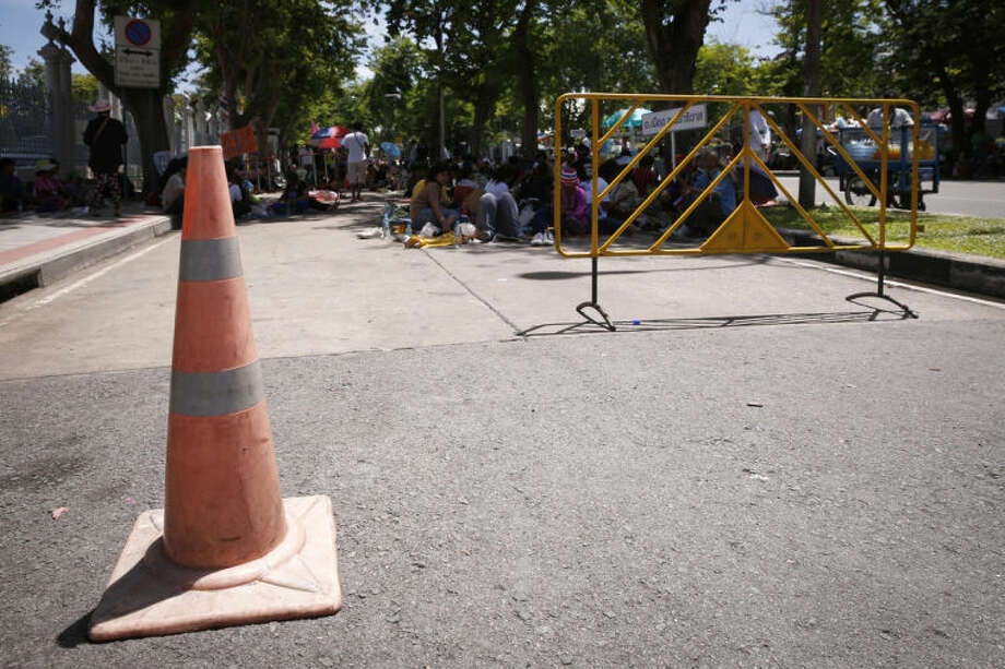 A cone stands as anti-government protesters, background, wait for a rally outside Parliament House in Bangkok, Thailand, Wednesday, May 14, 2014. Move a traffic cone placed by people who have spent six months taking over various areas of this politically volatile capital and you could get beaten, stabbed or shot. For many Thais sick of the chaos, it is a chilling thought, but also a chance to meme. Allegations that anti-government protesters have attacked several motorists for moving traffic cones have sparked a mix of outrage and creativity in political cartoons and online postings that went viral this week. (AP Photo/Vincent Thian)