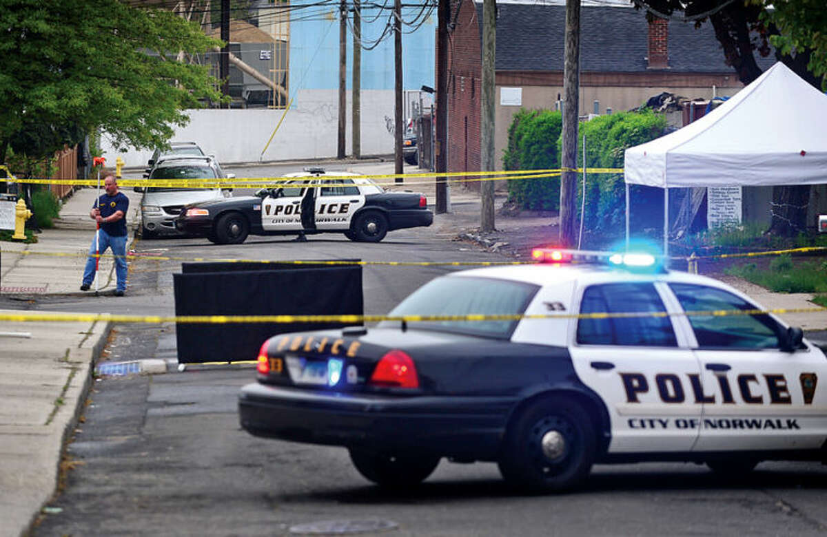 Hour photo / Erik Trautmann Norwalk police investigate the first homicide in 17 months on Isaacs and Leonard Streets Thursday morning.