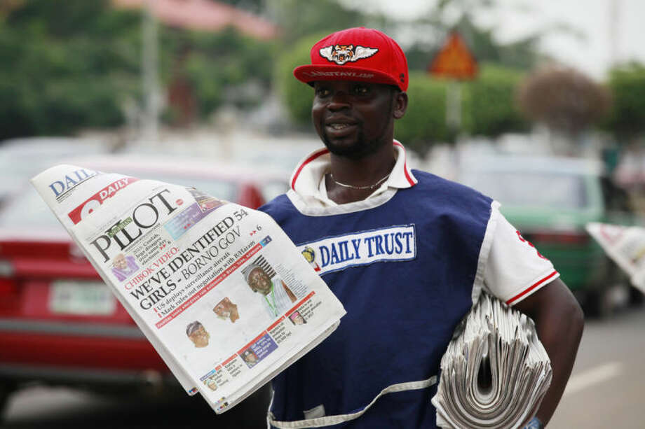 "A vendor sell local newspapers on a street, with headlines stating we have identified 54 of the kidnapped school girls of a government secondary school Chibok, in a video released on Monday by Boko haram in Abuja, Nigeria, Wednesday, May 14, 2014. A Nigerian government official said ""all options are open"" in efforts to rescue almost 300 abducted schoolgirls from their captors as US reconnaissance aircraft started flying over this West African country in a search effort. Boko Haram, the militant group that kidnapped the girls last month from a school in Borno state, had released a video yesterday purporting to show some of the girls. A civic leader said representatives of the missing girls' families were set to view the video as a group later today to see if some of the girls can be identified. (AP Photo/Sunday Alamba)"