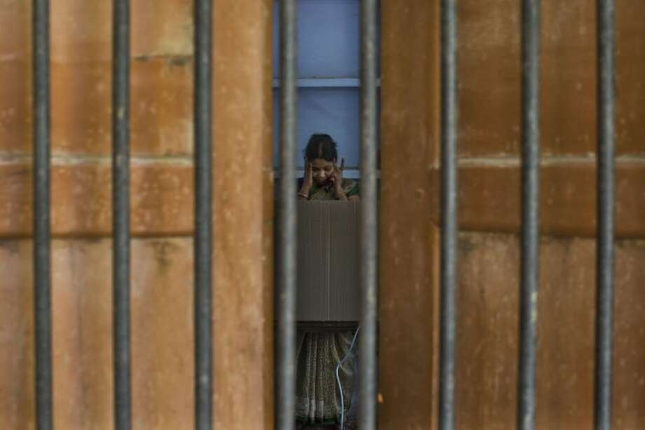 AP10ThingsToSee - A woman pauses before casting her vote at a polling station on the final day of polling in Varanasi, in the northern Indian state of Uttar Pradesh, Monday, May 12, 2014. Millions of Indian voters wrapped up a mammoth national election Monday. (AP Photo/Bernat Armangue)