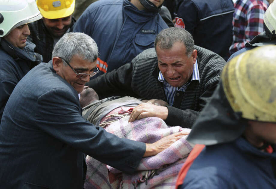 A man cries over the body of a miner being carried outside the coal mine in Soma, Turkey, Wednesday, May 14, 2014. Rescuers desperately raced against time to reach more than 200 miners still trapped underground Wednesday after an explosion and fire at the coal mine on Tuesday killed at least 238 workers. (AP Photo/Depo Photos)