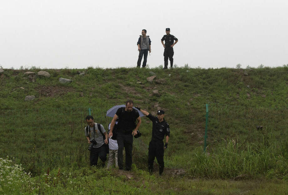 Journalists going to the capsized cruise ship area is ordered to leave by policemen along the Yangtze River in Jianli in central China's Hubei province, Tuesday, June 2, 2015. Divers on Tuesday pulled several survivors from inside the capsized cruise ship and searched for other survivors, state media said, giving some small hope to an apparently massive tragedy. (AP Photo/Andy Wong)