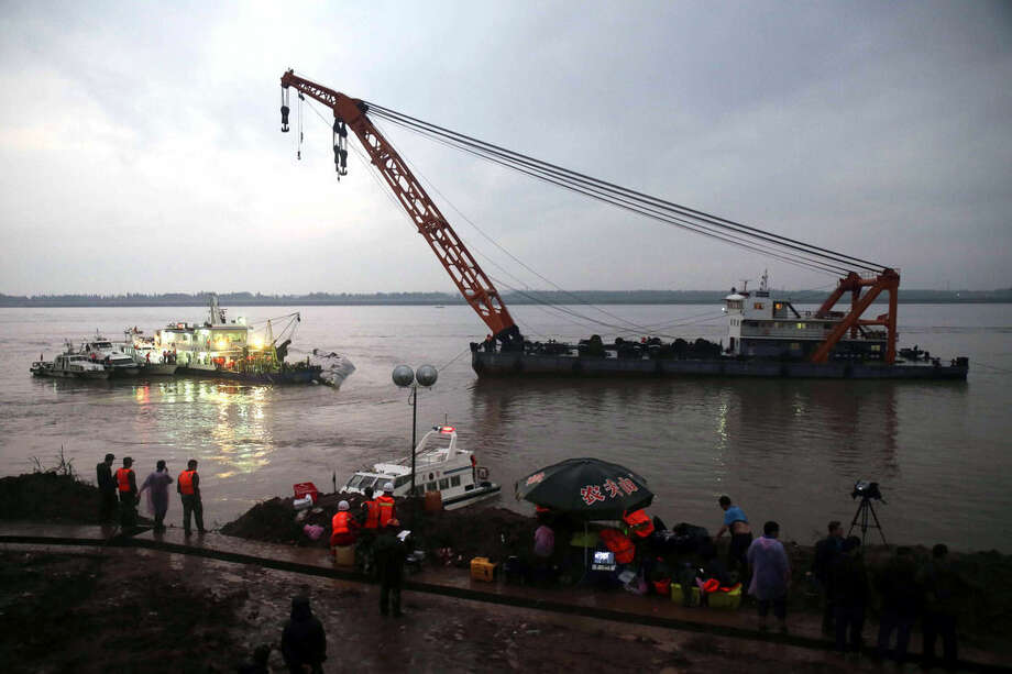 A crane is positioned near a capsized ship on the Yangtze River in Jianli in central China's Hubei province Tuesday June 2, 2015. Divers on Tuesday pulled three people alive from inside an overturned cruise ship and searched for other survivors, state media said, giving some small hope to an apparently massive tragedy with well over 400 people still missing on the Yangtze River. (Chinatopix Via AP) CHINA OUT