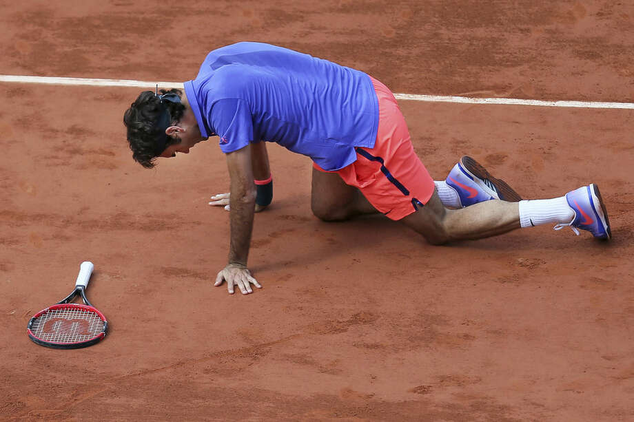 Switzerland's Roger Federer gets up after slipping in the quarterfinal match of the French Open tennis tournament against Switzerland's Stan Wawrinka at the Roland Garros stadium, in Paris, France, Tuesday, June 2, 2015. (AP Photo/David Vincent)