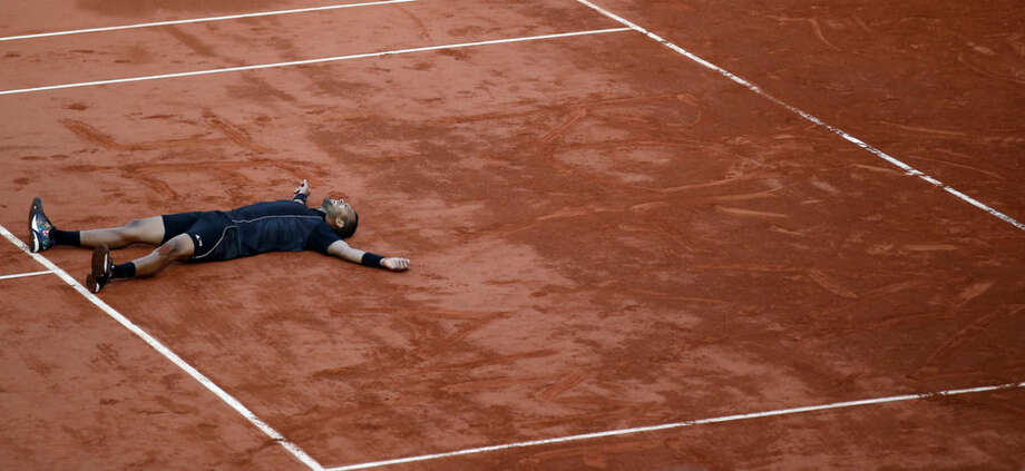 "France's Jo-Wilfried Tsonga lies after drawing ""Roland Je t' time"" (Roland I love you) on the court after defeating Japan's Kei Nishikori during their quarterfinal match of the French Open tennis tournament at the Roland Garros stadium, Tuesday, June 2, 2015 in Paris. (AP Photo/Michel Euler)"