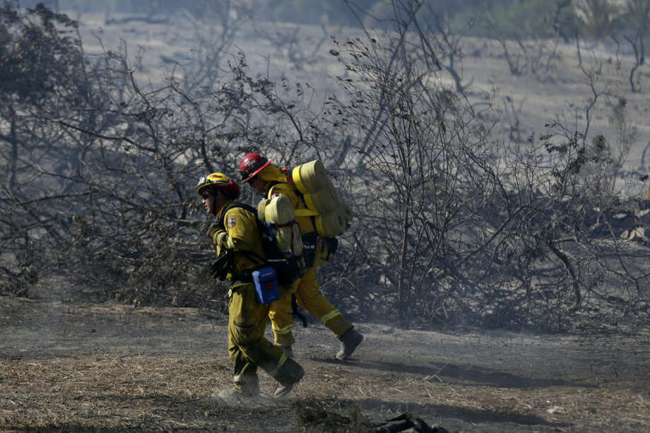Firefighters make hike through burned vegetation during a wildfire Wednesday, May 14, 2014, in Carlsbad, Calif. Flames engulfed suburban homes and shot up along canyon ridges in one of the worst of several blazes that broke out Wednesday in Southern California during a second day of a sweltering heat wave, taxing fire crews who fear the scattered fires mark only the beginning of a long wildfire season. (AP Photo)
