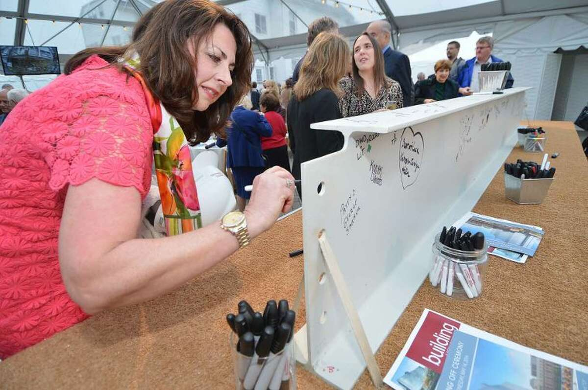 Hour Photo/Alex von Kleydorff Stamford Hospital COO Kathy Silard signs one of the beams during the Topping Off Ceremony for Stamford Hospitals new facility