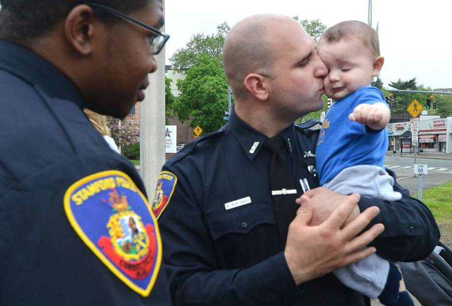 Hour Photo/Alex von Kleydorff Police Officer Michael Montanaro gives his 6 month old son Michael vVito Montanaro during Peace Officers Memorial Day service at Stamford Police Headquaters