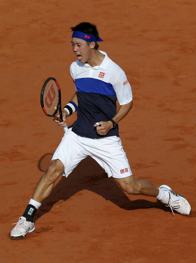 Japan's Kei Nishikori clenches his fist after scoring a point as he plays France's Jo-Wilfried Tsonga during their quarterfinal match of the French Open tennis tournament at the Roland Garros stadium, Tuesday, June 2, 2015 in Paris, France. (AP Photo/Michel Euler)