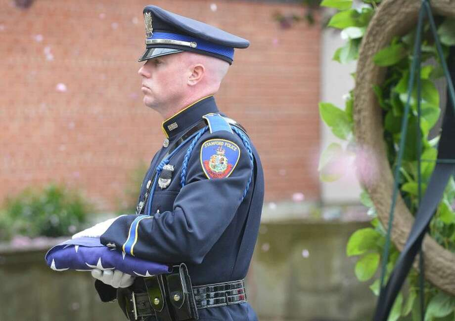 Hour Photo/Alex von Kleydorff Leaves from a flowering tree fall as Police Officer Chris Brown prepares to raise the new flag during Stamford's Peace Office Memorial Day service