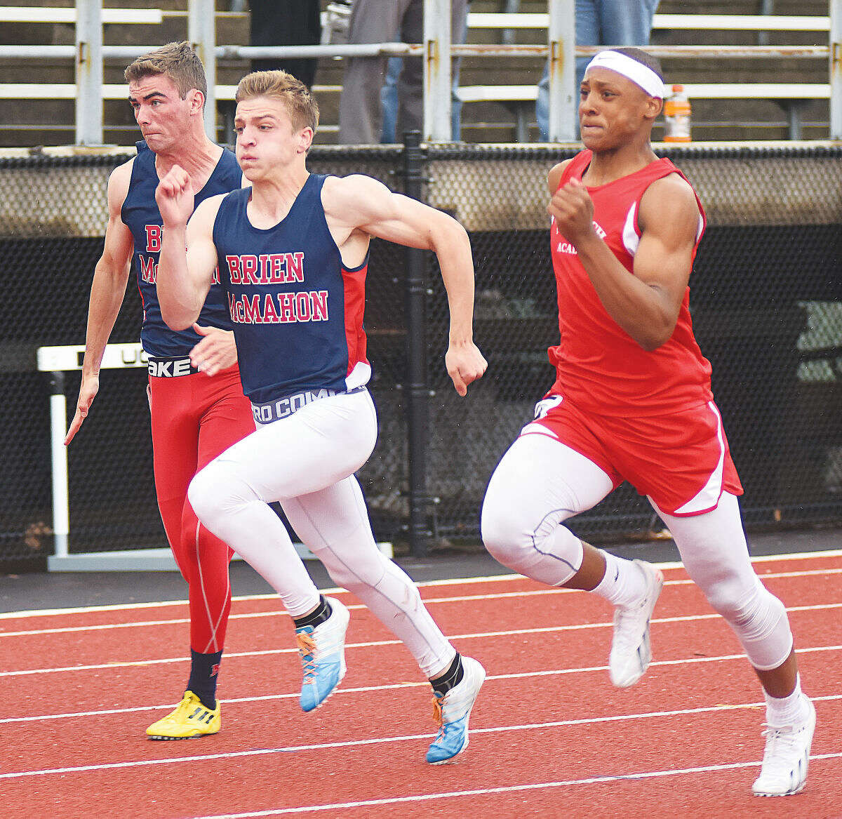Hour photo/John Nash - McMahon's Niko Petridis, center, and Daniel Linehan, left, competes in the boys 100-meter dash finals against Norwich Free Academy's Jawaun Johnson, right.