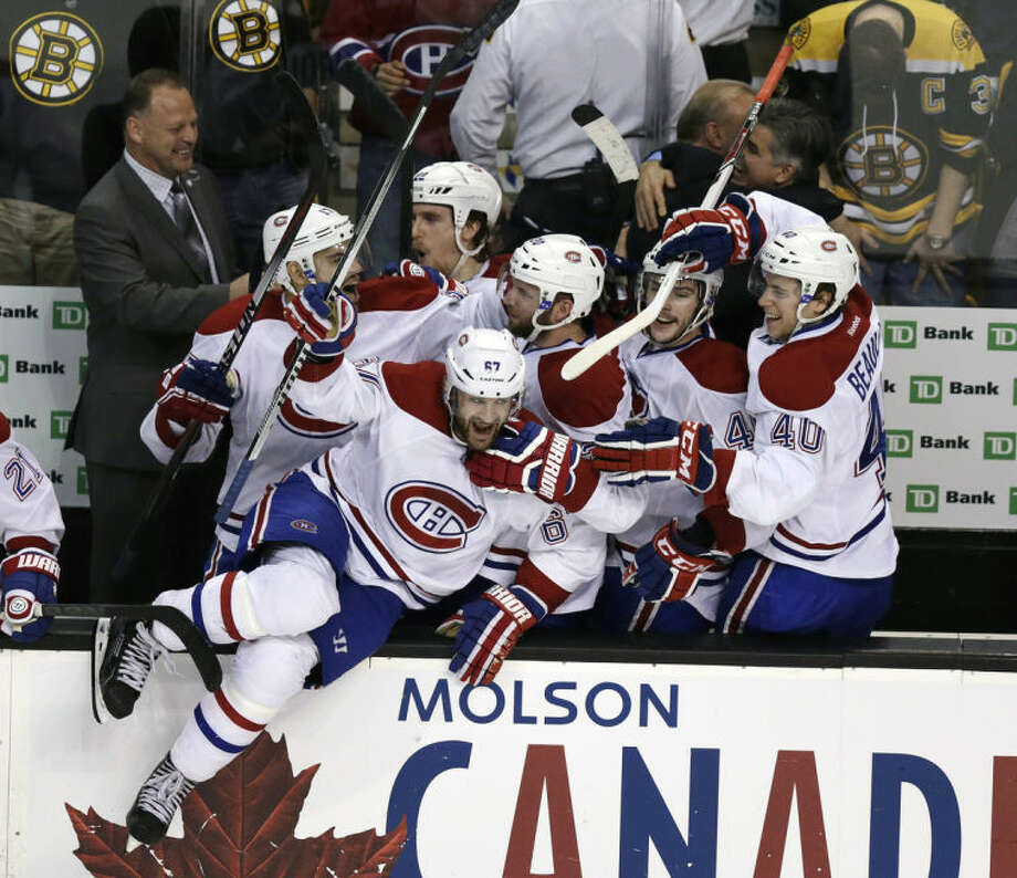 Montreal Canadiens left wing Max Pacioretty (67) leaps from the bench as teammates celebrate a 3-1 win over the Boston Bruins in Game 7 of a second-round NHL hockey Stanley Cup playoff series, in Boston on Wednesday, May 14, 2014. The Canadiens advanced to the Eastern Conference finals against the New York Rangers. (AP Photo)