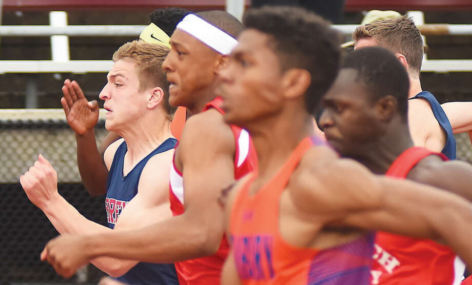 Hour photo/John Nash - Brien McMahon's Niko Petridis, left, runs with the pack during the boys 100-meter dash final at Tuesday's Class LL track championship meet in New Britain.