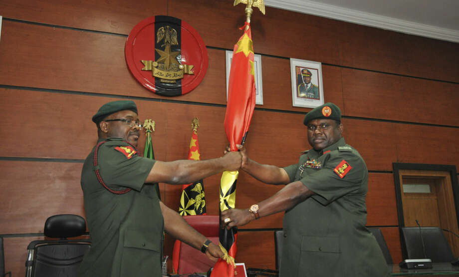 FILE - In this Monday, Jan. 20, 2014 file photo, Former chief of Army staff, Lt. Gen. Azubuike Ihejirika, left, holds a flag with Maj. Gen. Kenneth Tobiah Jacob Minimah, the newly appointed chief of army staff, during the handover ceremony in Abuja, Nigeria. Nigerian military abuses caused the deaths of some 8,000 people in the fight against Boko Haram extremists, Amnesty International said Wednesday, June. 3, 2015 in a report naming senior officers it wants investigated for alleged war crimes. (AP Photo/Olamikan Gbemiga File)
