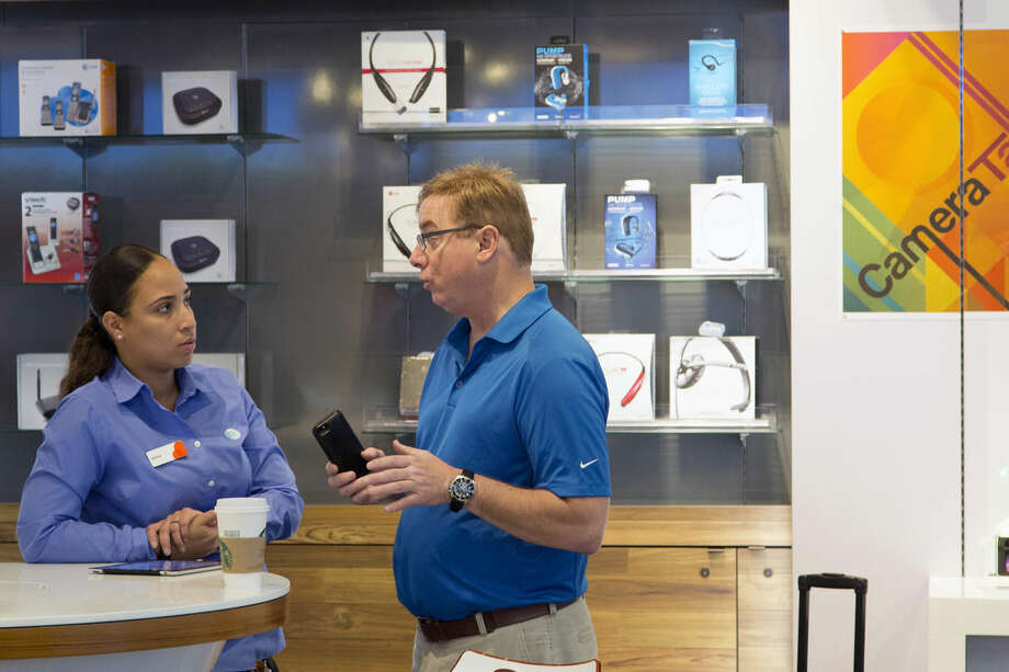 In this May 6, 2015, photo, an AT&T employee, left, works with a customer at a company store in New York. Upgrading your phone is no longer as simple as paying $100 or $200 and extending your service contract by two years. (AP Photo/Mark Lennihan)
