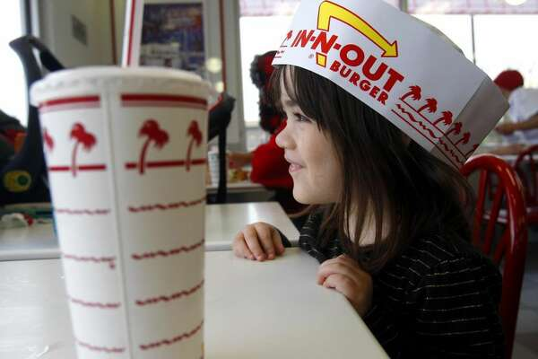 Rylee Jones wears a paper hat as she attends the grand opening Thursday Nov. 20, 2014 of San Antonio's first In-N-Out Burger. ( Photo: William Luther, San Antonio Express-News)