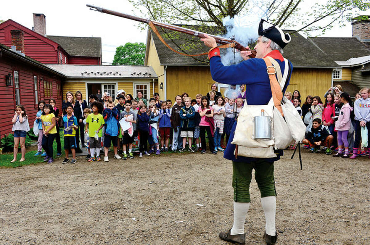 Hour photo / Erik Trautmann Renactor Dan Kinley fires a musket for Cider Mill Elementarty School fourth graders who went on their annual trip to the Wilton Historical Society to experience colonial life Thursday.