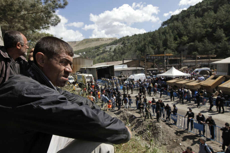 People wait outside the mine in Soma, western Turkey, Thursday, May 15, 2014. An explosion and fire at a coal mine in Soma, some 250 kilometers (155 miles) south of Istanbul, killed hundreds of workers, authorities said, in one of the worst mining disasters in Turkish history. (AP Photo/Lefteris Pitarakis)