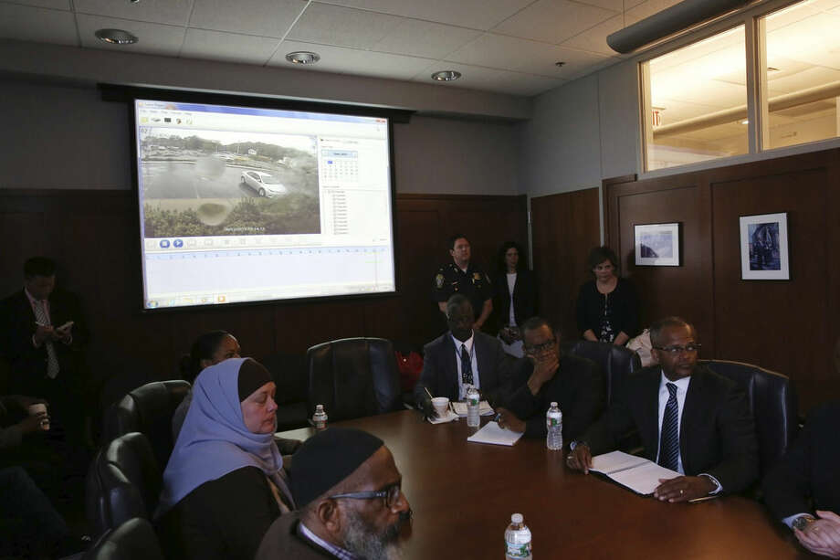 Community members and police officials at Boston Police Department Headquarters prepare to see a video, Wednesday, June 3, 2015, in Boston, of a fatal police shooting on Tuesday, in the city's Roslindale neighborhood. Police said the video shows that officers did not have their weapons drawn when they approached Usaama Rahim and that they backed up when he initially lunged at them with a knife. (David Ryan/The Boston Globe via AP, Pool)