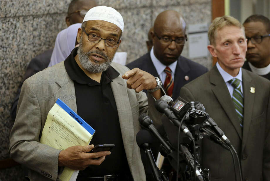 Abdullah Faaruuq, Imam of the Mosque for the Praising of Allah, left, speaks to reporters during a news conference as Darnell Williams, president of the Urban League of Eastern Massachusetts, behind center, Boston Police Commissioner William Evans, front right, and Rev. Arthur Gerald, Jr., president of the Black Ministerial Alliance of Greater Boston, right, look on during a news conference, Wednesday, June 3, 2015, at Boston Police Headquarters, in Boston. Boston police said they have video showing Usaama Rahim, a man who was under 24-hour surveillance by terrorism investigators, lunging with a knife at a police officer and an FBI agent before he was shot and killed. (AP Photo/Steven Senne)