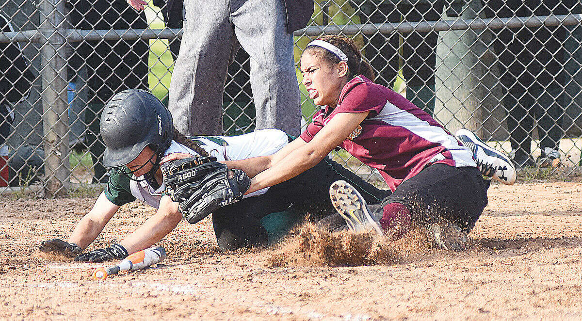 Hour photo/John Nash - Norwalk's Katie Sciglimpaglia, left, reaches for home plate with the tying run after colliding with New Britain pitcher Destini Kennedy in the bottom of the seventh inning of Wednesday's CIAC Class LL softball game at Ray Barry Field in Norwalk. The Bears walked off withi an 8-7 win.