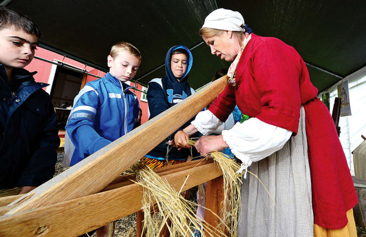 Hour photo / Erik Trautmann Renactor Kate Duckin helps Cider Mill Elementarty School fourth graders Christian Stevens, Robert Caruso and Max Mercado crack flax after their class went on their annual trip to the Wilton Historical Society to experience colonial life Thursday.
