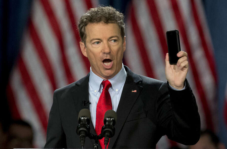 FILE - In this April 7, 2015 file photo, Sen. Rand Paul, R-Ky. holds up his cell phone as he speaks before announcing the start of his presidential campaign, in Louisville, Ky. Key Patriot Act anti-terror provisions, including bulk collection of Americans' phone records, expire at midnight unless senators come up with an 11th hour deal in an extraordinary Sunday afternoon session. (AP Photo/Carolyn Kaster, File)