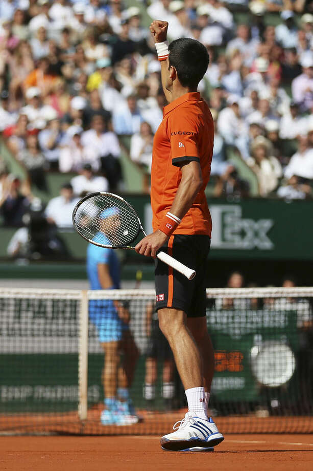 Spain's Rafael Nadal, rear in blue, watches as Serbia's Novak Djokovic clenches his fist after scoring a point in the quarterfinal match of the French Open tennis tournament against at the Roland Garros stadium, in Paris, France, Wednesday, June 3, 2015. Djokovic won in three sets 7-5, 6-3, 6-1. (AP Photo/David Vincent)