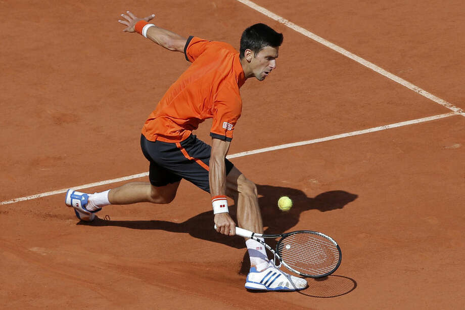 Serbia's Novak Djokovic returns in the quarterfinal match of the French Open tennis tournament against Spain's Rafael Nadal at the Roland Garros stadium, in Paris, France, Wednesday, June 3, 2015. (AP Photo/Christophe Ena)