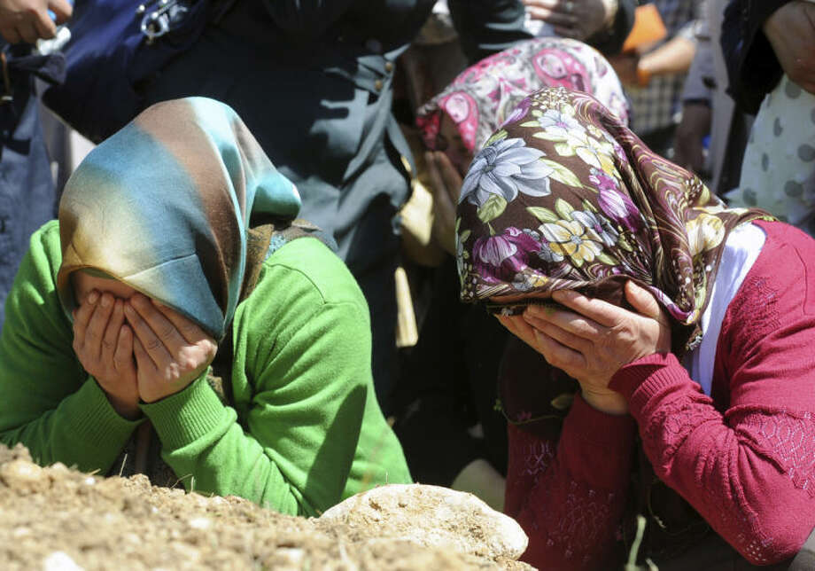 Family members cry during the funerals of mine accident victims in Soma, Turkey, Thursday, May 15, 2014. An explosion and fire at a coal mine in Soma, some 250 kilometers (155 miles) south of Istanbul, killed hundreds of workers, authorities said, in one of the worst mining disasters in Turkish history.(AP Photo/Emre Tazegul)