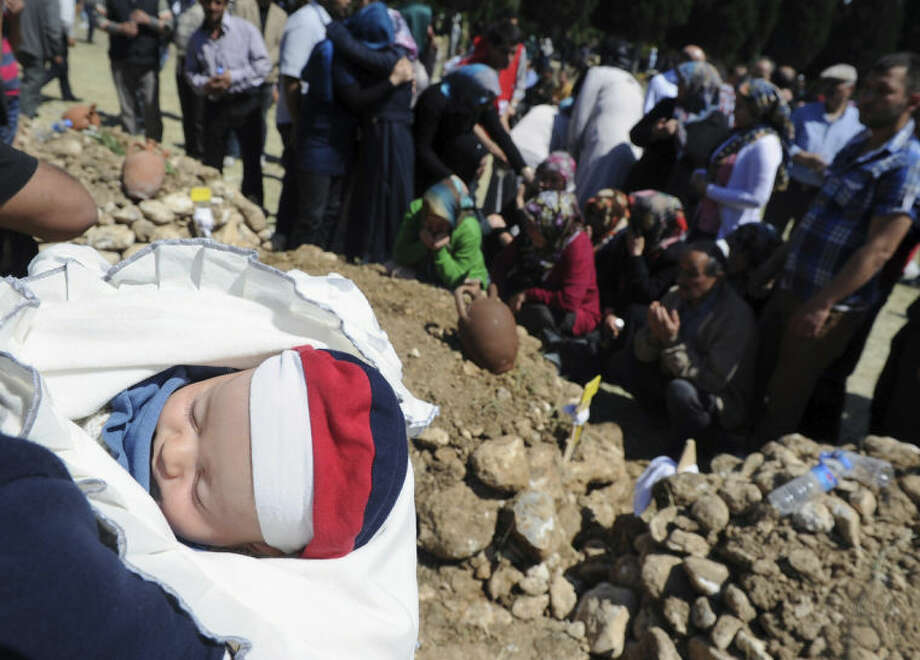 A baby sleeps, as people pray during the funeral of a victim from the mine accident, in Soma, Turkey, Thursday, May 15, 2014. An explosion and fire at a coal mine in Soma, some 250 kilometers (155 miles) south of Istanbul, killed hundreds of workers, authorities said, in one of the worst mining disasters in Turkish history. (AP Photo/Emre Tazegul)